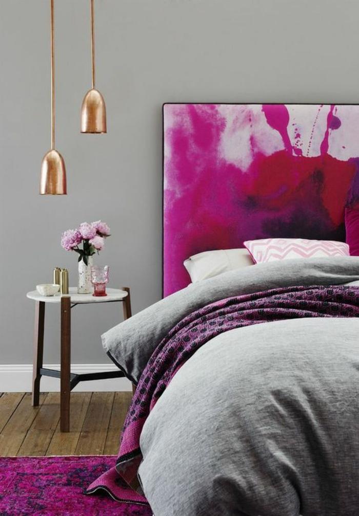 une suspension chevet double en cuivre installée au-dessus d'une table de chevet en marbre et bois, une tête de lit en tissu artistique