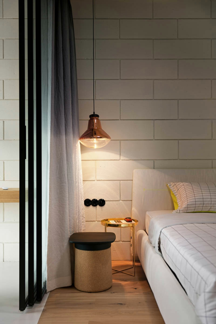 un grand luminaire suspension à finition cuivre avec un câble noir, une chambre à coucher au design industriel