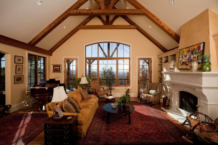 cheminee en pierre, mur couleur jaune, tapis oriental, canapé fauve, table basse en bois, piano, cadre décoratif peinture multicolore, vue paysage forestier
