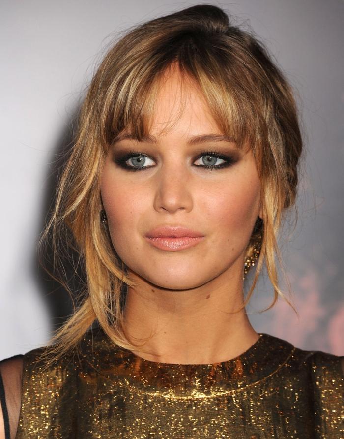 maquillage smoky, cheveux blonds, robe dorée à manches courtes, lèvres rose, boucles d'oreilles, Jennifer Lawrence