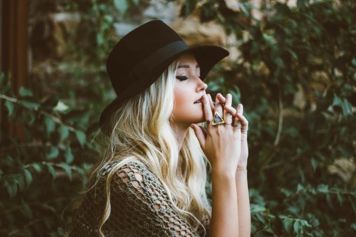 blond californien, hippie style, capeline noire femme, eye liner, bague triangulaire, cheveux longs bouclés
