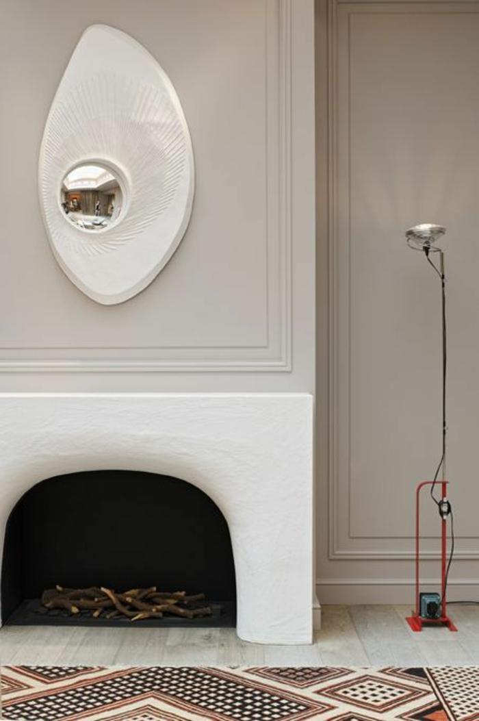 oeil de sorciere au cadre modernistique abstrait en blanc au dessus d'une cheminee rustique toute blanche