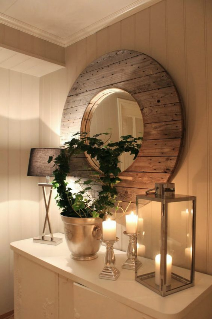 grand miroir oeil de sorciere iluminé par des bougies blanches