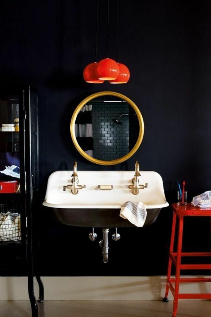 oeil de sorciere au cadre doré combiné avec un lavabo blanc et des luminaires rouges
