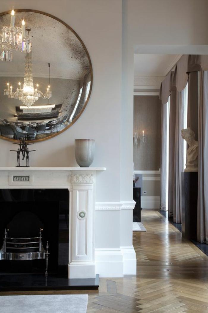 miroir oeil de sorcière dans un intérieur de style chateau au dessu d'une cheminée blanche et lustre en cristal réflechi