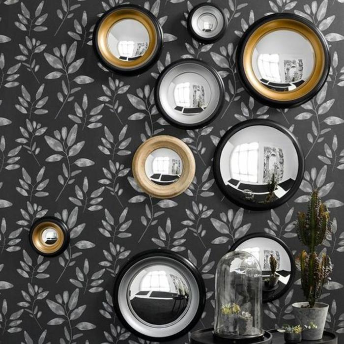 miroir doré sur un mur gris aux feuilles blanches entrée miroirs oeil de sorciere aux tailles diverses
