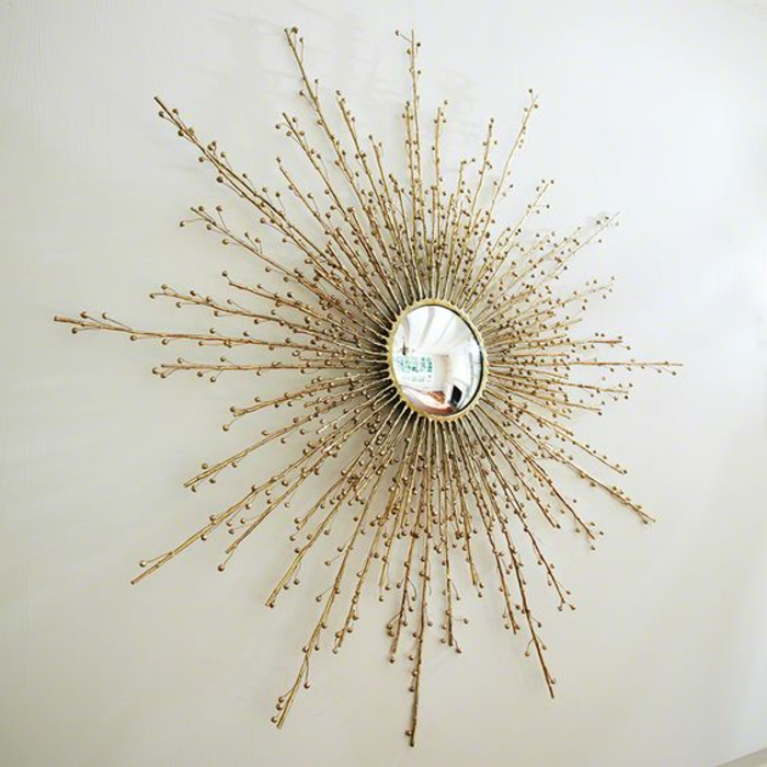 miroir soleil aux rayons fins stylisés petite partie pour réflechir la lumière sur mur blanc
