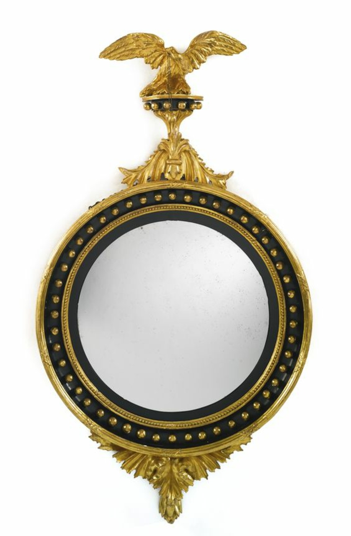 miroir de sorcière dans un style impérial avec un aigle au dessus cadre doré