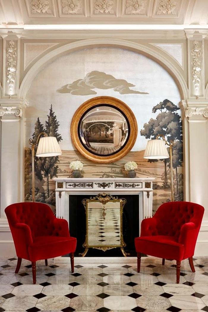miroir vintage oeil de sorcière sur un mur peint avec un tableau de nature foret et champs et deux fauteuils rouges classiques des deux cotés de la cheminée