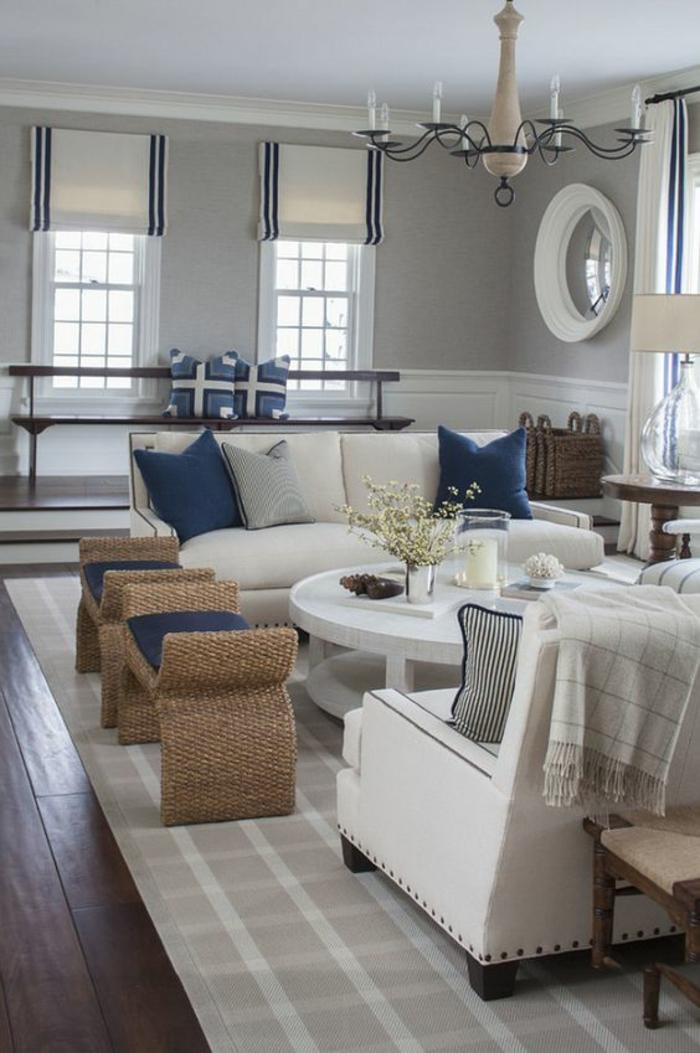 oeil de sorciere au cadre blanc dans un intérieur aux murs blancs avec des coussins pour les meubles en bleu