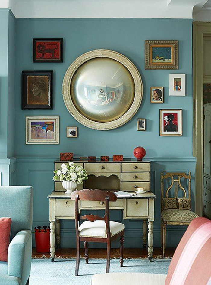 miroir oeil de sorcière miroir grand rond avec cadre blanc sur un mur bleu avec des tableaux en mini cadres