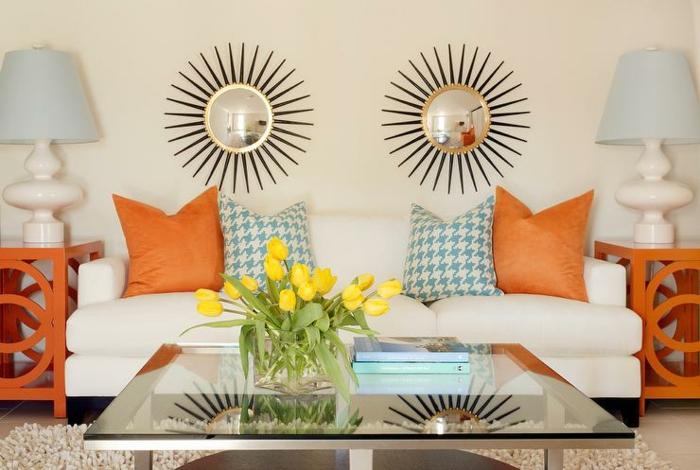 miroir soleil deux au dessus du canapé blanc avec des coussins colorés et aux motifs pépites