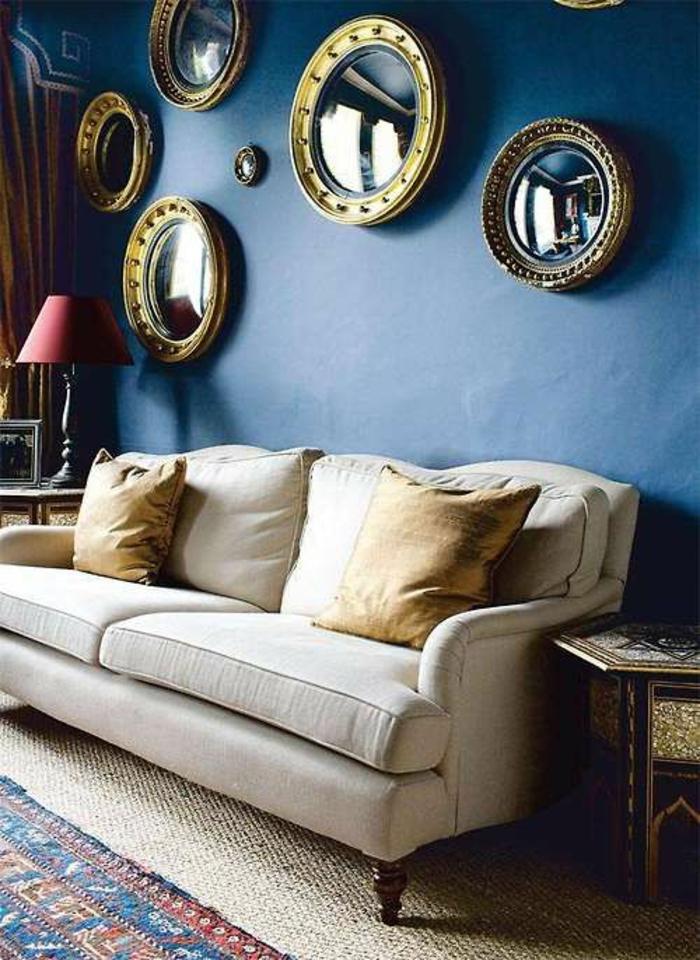 oeil de sorciere miroir 7 pièces sur un mur bleu marin au dessus d'un canapé blanc avec des coussins jaunes