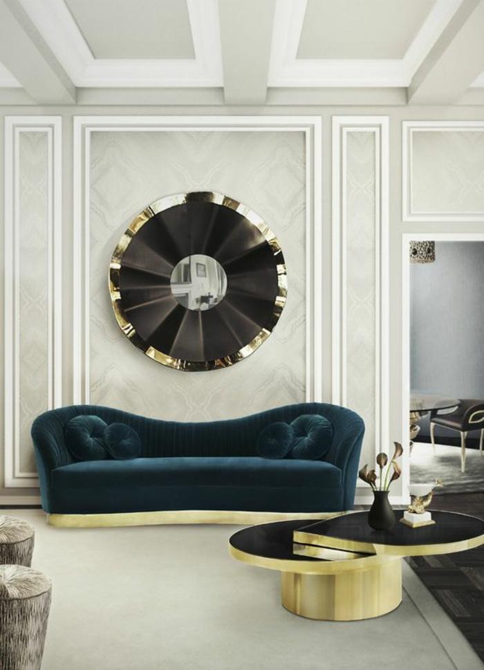 grand miroir soleil au cadre en noir et couleur or installé sur un mur en gris clair