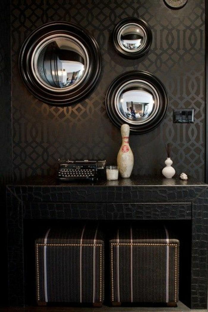 miroir oeil de sorcière sur un mur noir trois miroirs au cadre noir et sur in mur d'un noir légèrement plus clair