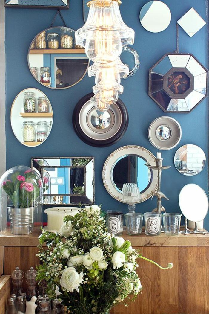 miroir de sorcière un mur entier avec des miroirs de toutes tailles et formes avec des lustres en cristal modernes
