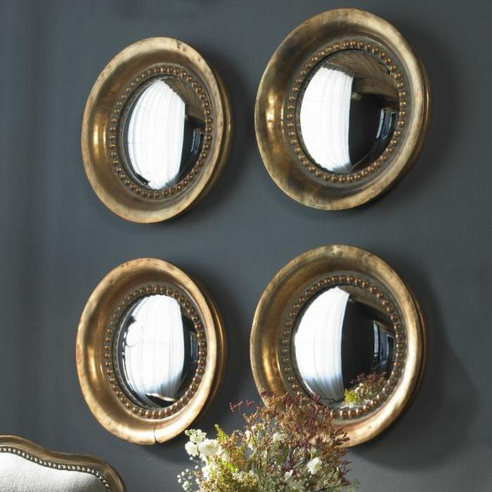 miroir oeil de sorcière quatre éléments sur un mur gris fumée pour réflechir joliment la lumière venante des fenetres