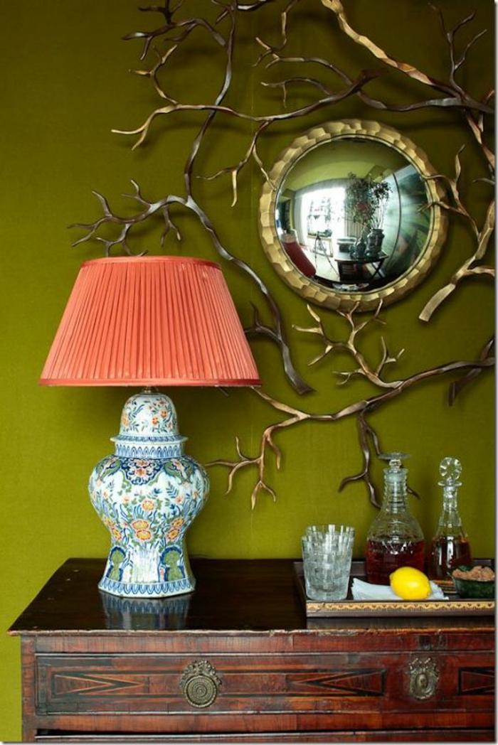 miroir doré petite taille dans l'entrée à coté d'un lampadaire pour table au tissu plissé en couleur corail