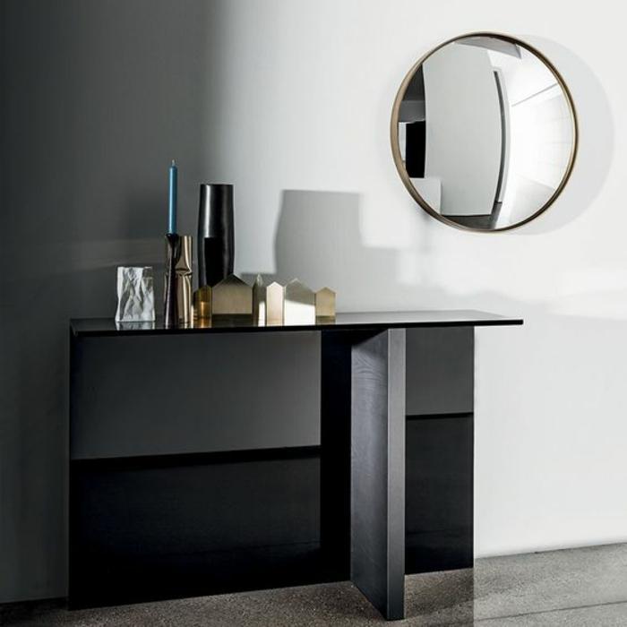 miroir oeil de sorciere tout rond et grand dans l'entrée au dessus d'un meuble en noir