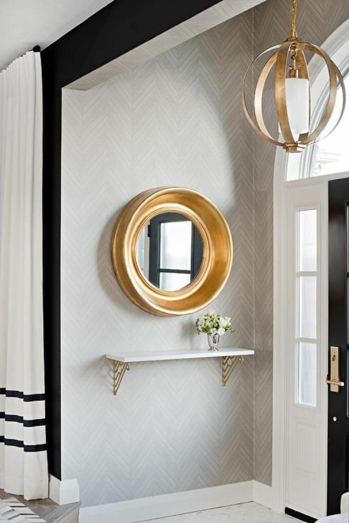 miroir sorcière ancien au cadre massif doré en forme ronde dana une entrée raffinée
