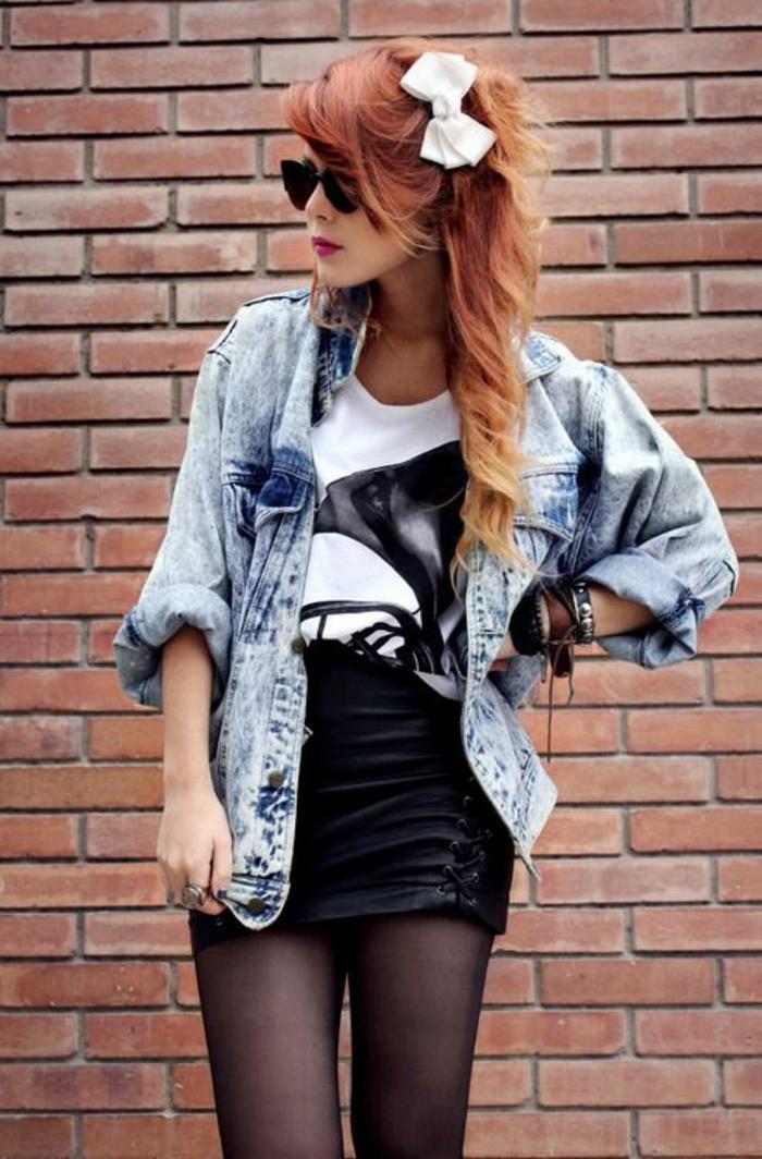 mode année 80 Madonna style avec noeud blanc dans les cheveux et mini jupe en cuir noir avec des ficelles de cote