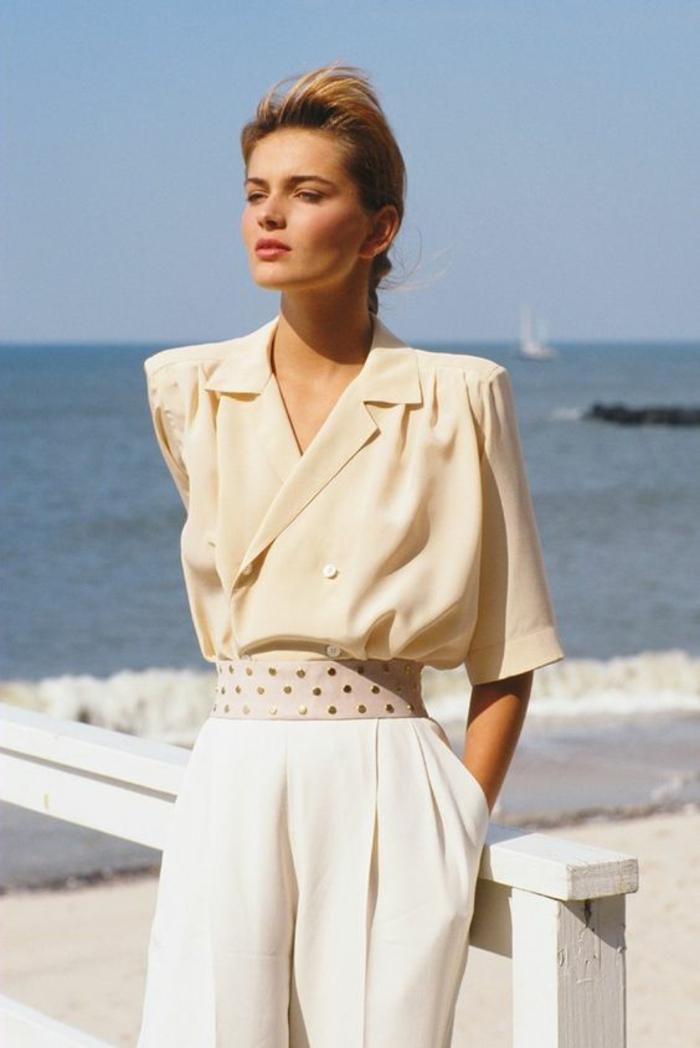 mode année 1980 femme pantalon blanc et chemisier manches 3/4 avec épaulettes et taille fortement soulignée
