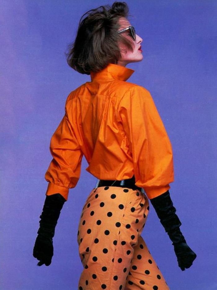 mode année 80 en orange pantalon à pois noirs et chemisier manches chauve-souris col haut