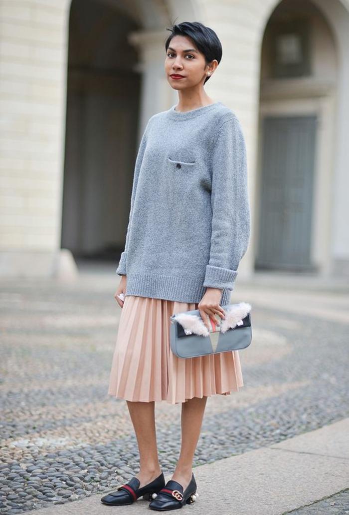 mode année 80 gros pull en gris avec jupe plissée couleur melon et des mocassins en noir et rouge avec sac pochette en gris et blanc et accent en peluche blanche