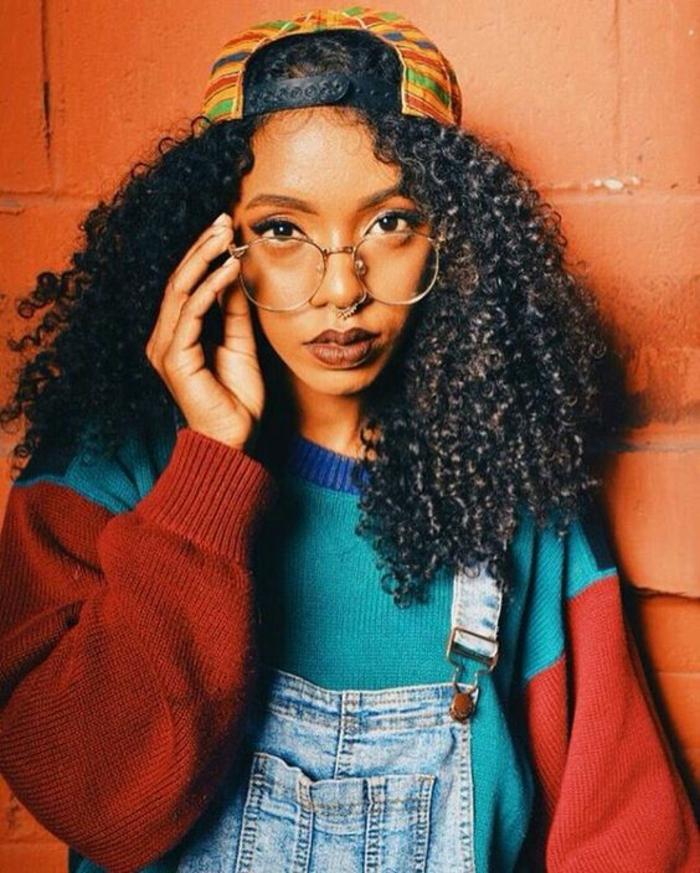 mode année 80 salopette en jean denim clair lunette de vue forme ronde et casquette aux motifs afro