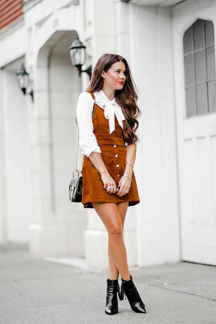 mode année 80 mini robe salopette en marron clair avec blouse blanche au gros noeud et des bottines noires
