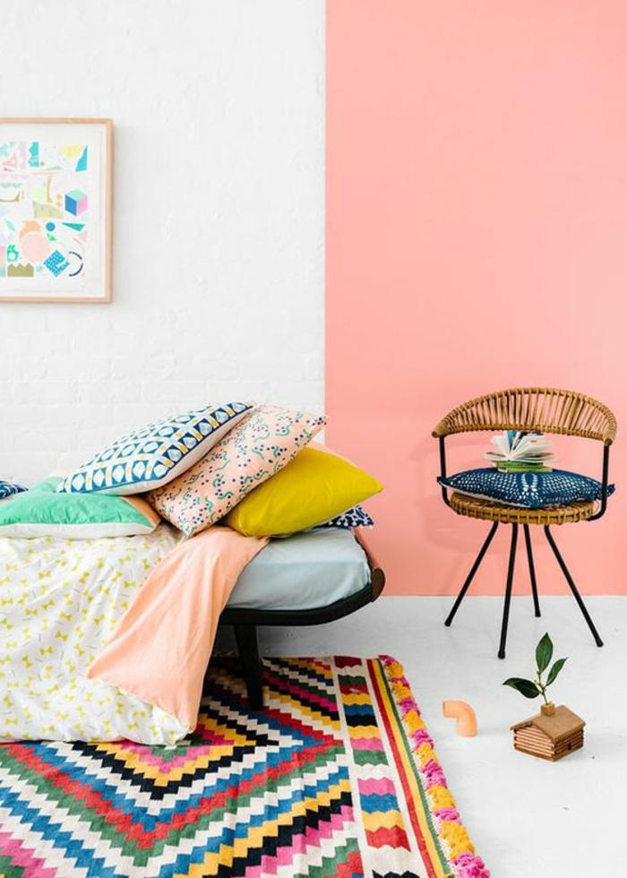 mur couleur abricot et blanc, carpette colorée, coussins décoratifs, chaise en rotin