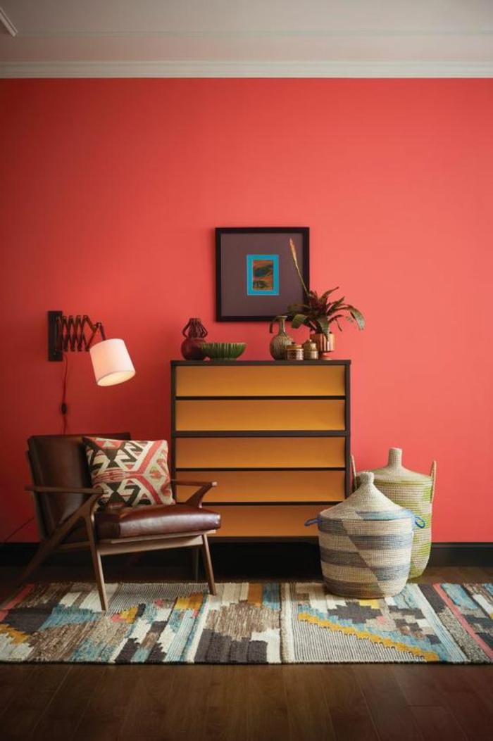 mur couleur rouge corail, carpette bariolée, paniers et chaise en cuir et bois