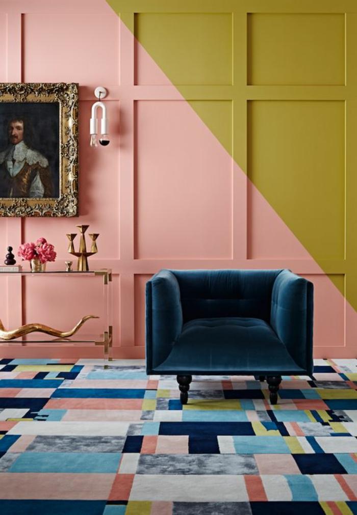 mur couleur corail et vert, petit sofa bleu, tapis géométrique, portrait ancien