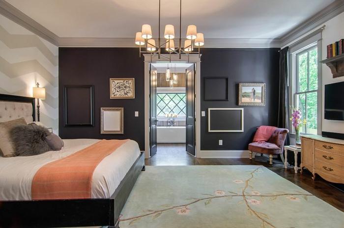 lit en bois marron, couverture de lit orange, coussins gris, mur d accent marron foncé, deco cadre vide et tableaux de peinture, fauteuil rose, meuble tv en bois vintage