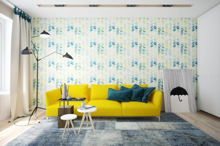 salon scandinave, mur habillé de papier peint à motifs floraux, bleu, jaune et vert, canapé jaune, tapis gris et bleu, tables scandinaves, parquet clair, lampe design