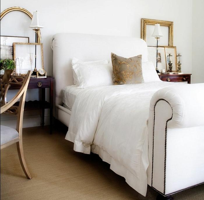 deco cadre vide, mur et linge de lit couleur blanche, revêtement sol marron clair, chaise en bois, tables de nuit en bois elegants, photos et dessins encadrés