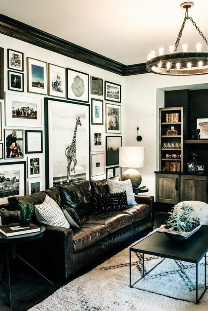 cadre rectangulaire, table ronde, lustre en ampoules, bibliothèque en bois, poster girafe
