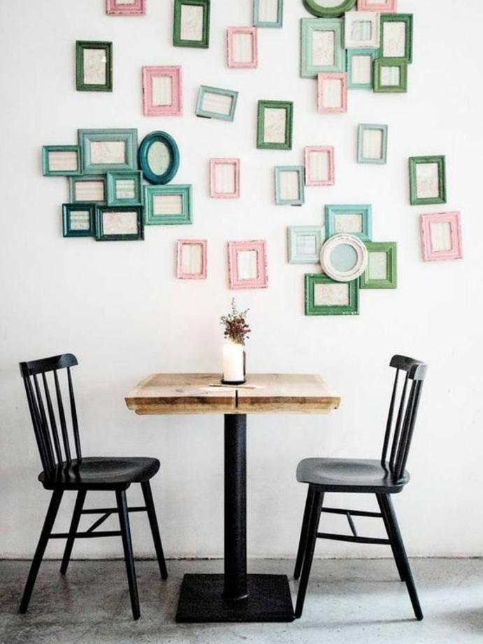 chaises en métal et table en bois et métal, deco cadre vie, mur décoré de plusieurs petits cadres photos verts, bleus et rose, sol en béton ciré
