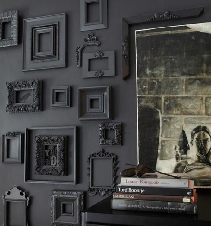 habiller un mur de cadres noirs rectangulaires, piles de livres, affiche decorative, comment décorer un salon en noir
