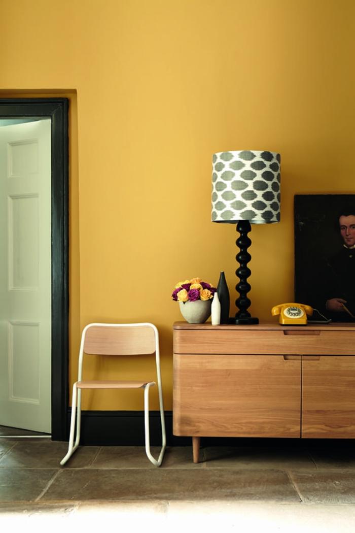 un salon d'esprit rétro, mur d'accent en ocre jaune associé avec mobilier en bois naturel