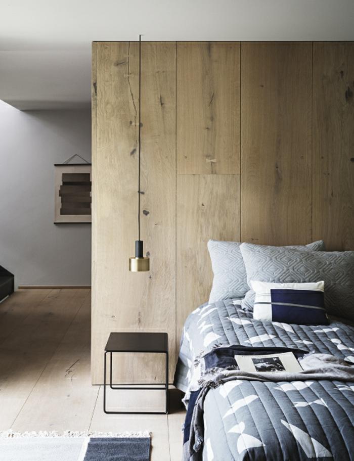 une suspension chevet bi-matière en parfaite harmonie avec le mur en planches de bois et la table de chevet minimaliste