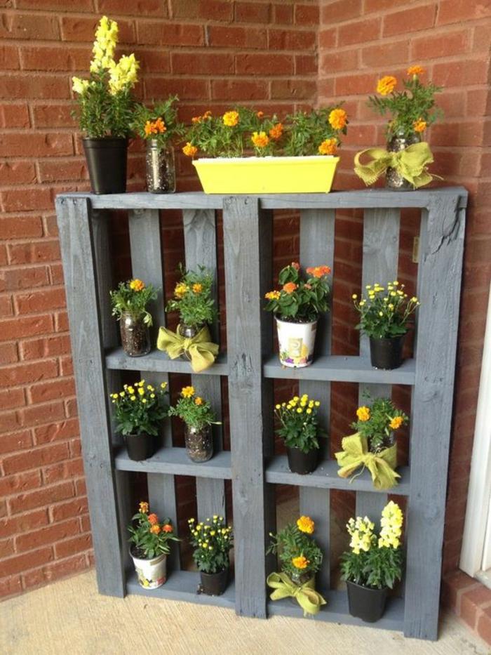 mur végétal en palette, palette grise avec plusieurs fleurs en pots et mur en briques