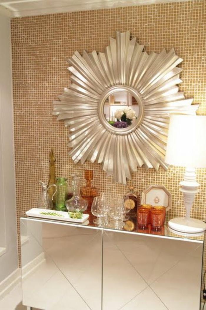 miroir de sorcière soleil aux grands rayons stylisés en couleur argent au-dessus d'un meuble en blanc laqué