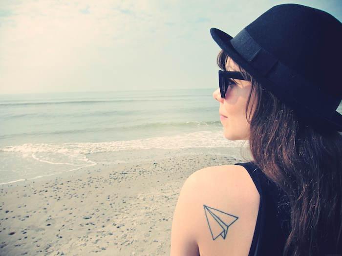 tatouage voyage avec avion papier tatoué sur l'omoplate femme