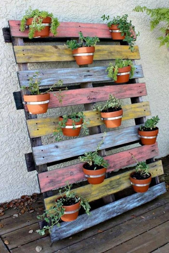 palette plante, pots de fleurs sur une palette dressée contre un mur