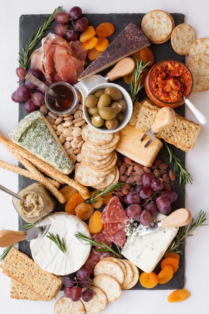 un plateau antipasti servi avec une variété de crackers et de fromages, trempette aux poivrons rouges pour accompagner le plateau