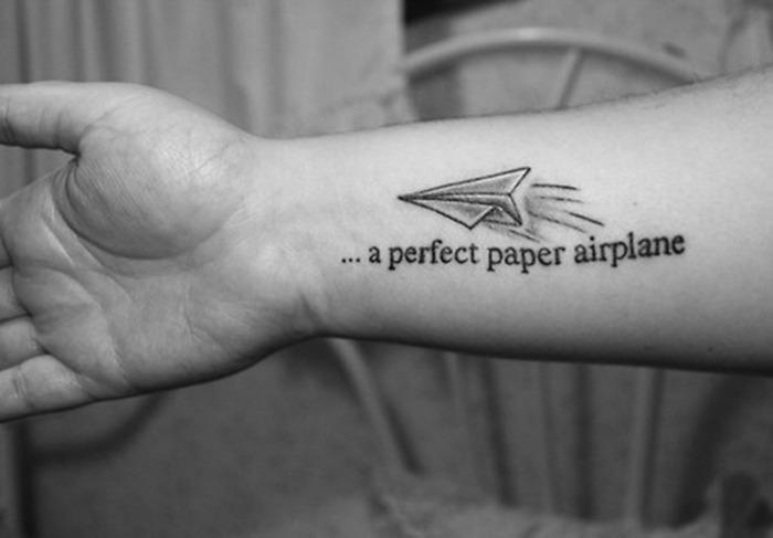grand tattoo avion papier sur avant bras phrase voyage citation vacances