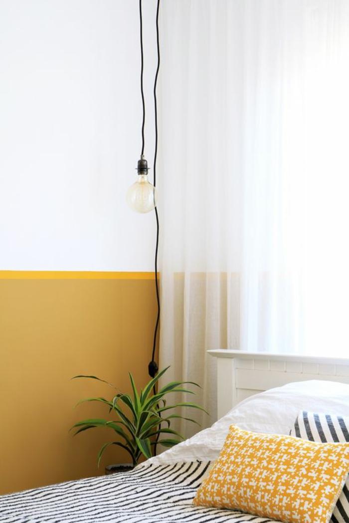 peinture ocre jaune en soubassement mise en valeur par les rideaux blancs et la lampe de chevet suspendue à ampoule nude