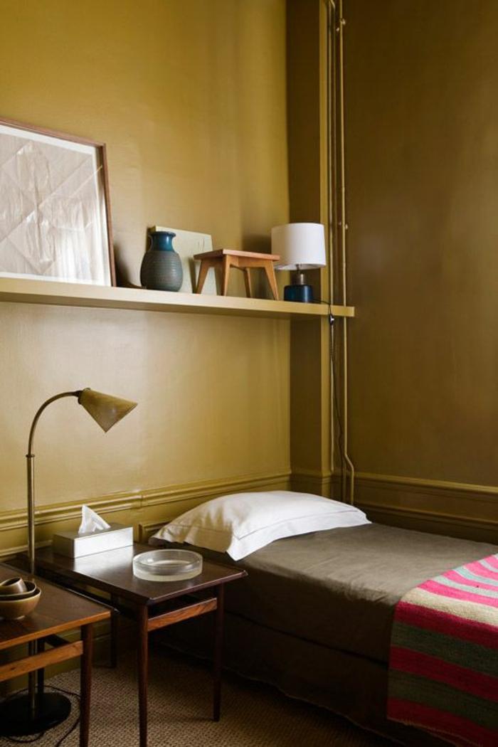 une chambre à coucher couleur jaune moutarde de style rétro, accents déco en bleu pétrole