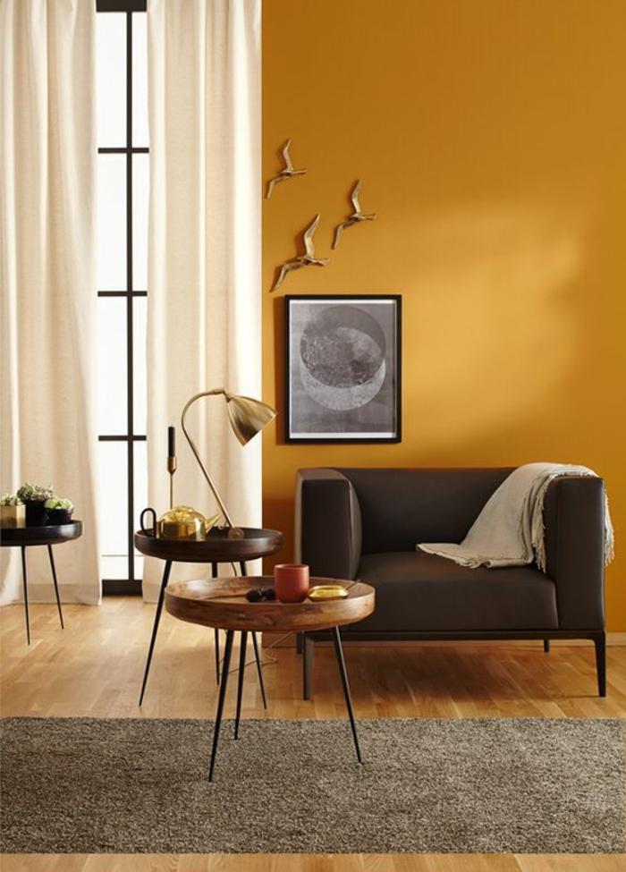 un mur d'accent ocre jaune pour réchauffer l'élégance classique d'un salon, contraste harmonieux entre la peinture ocre et les rideaux blancs